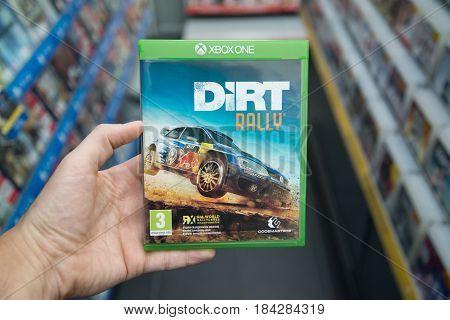 Bratislava, Slovakia, circa april 2017: Man holding Dirt Rally videogame on Microsoft XBOX One console in store