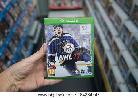 Bratislava, Slovakia, circa april 2017: Man holding NHL 17 videogame on Microsoft XBOX One console in store