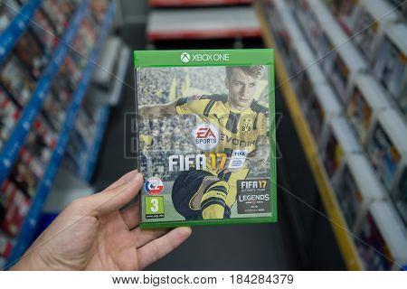 Bratislava, Slovakia, circa april 2017: Man holding Fifa 17 videogame on Microsoft XBOX One console in store