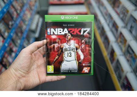 Bratislava, Slovakia, circa april 2017: Man holding NBA 2K17 videogame on Microsoft XBOX One console in store