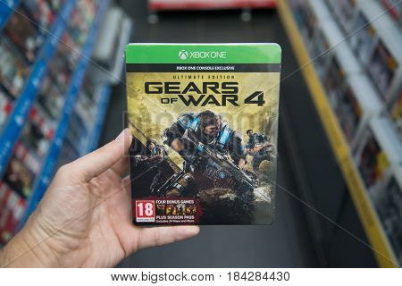 Bratislava, Slovakia, circa april 2017: Man holding Gears of War 4 Ultimate edition videogame on Microsoft XBOX One console in store