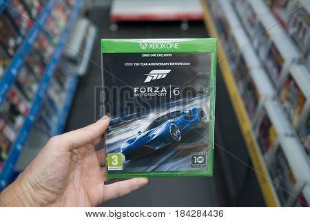 Bratislava, Slovakia, circa april 2017: Man holding Forza Motorsport 6 videogame on Microsoft XBOX One console in store