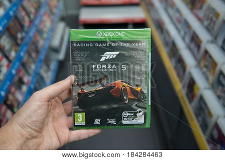 Bratislava, Slovakia, circa april 2017: Man holding Forza Motorsport 5 videogame on Microsoft XBOX One console in store