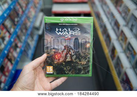 Bratislava, Slovakia, circa april 2017: Man holding Halo Wars 2 videogame on Microsoft XBOX One console in store