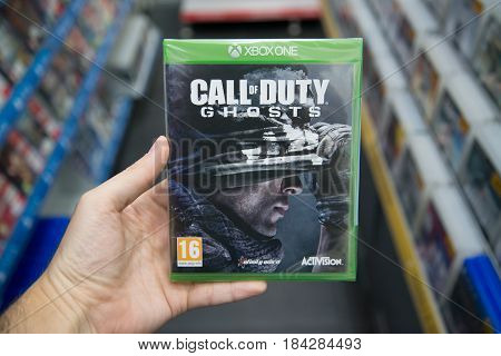 Bratislava, Slovakia, circa april 2017: Man holding Call of Duty Ghosts videogame on Microsoft XBOX One console in store