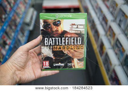 Bratislava, Slovakia, circa april 2017: Man holding Battlefield Hardline videogame on Microsoft XBOX One console in store