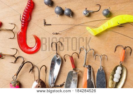 Different fishing tackles and plastic worms on wooden board background.