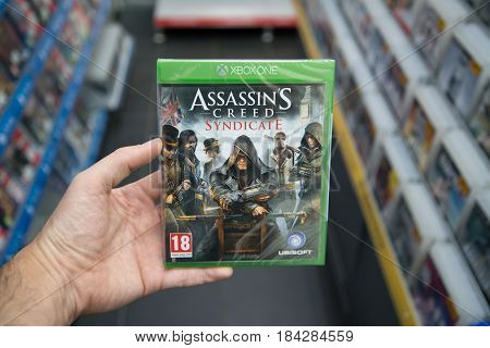 Bratislava, Slovakia, circa april 2017: Man holding Assassin's Creed Syndicate videogame on Microsoft XBOX One console in store