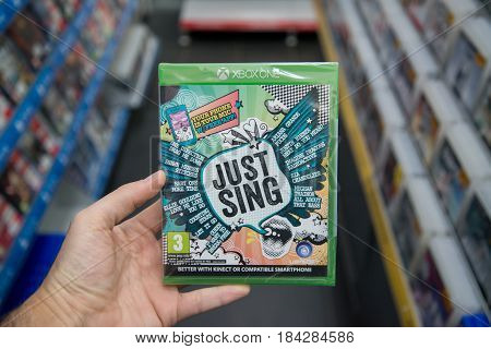 Bratislava, Slovakia, circa april 2017: Man holding Just sing videogame on Microsoft XBOX One console in store