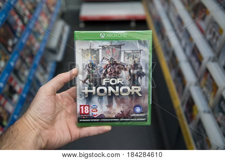 Bratislava, Slovakia, circa april 2017: Man holding For Honor videogame on Microsoft XBOX One console in store