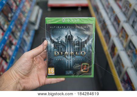 Bratislava, Slovakia, circa april 2017: Man holding Diablo 3 Reaper of Souls Ultimate evil edition videogame on Microsoft XBOX One console in store