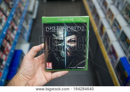 Bratislava, Slovakia, circa april 2017: Man holding Dishonored 2 videogame on Microsoft XBOX One console in store