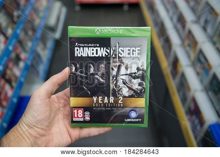 Bratislava, Slovakia, circa april 2017: Man holding Tom Clancy's Rainbow Six the Siege Year 2 gold edition videogame on Microsoft XBOX One console in store