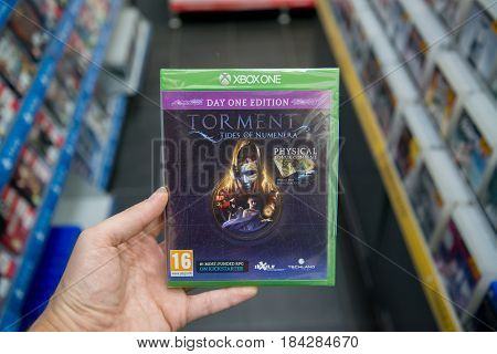 Bratislava, Slovakia, circa april 2017: Man holding Torment Tides of Numenera Day One edition videogame on Microsoft XBOX One console in store
