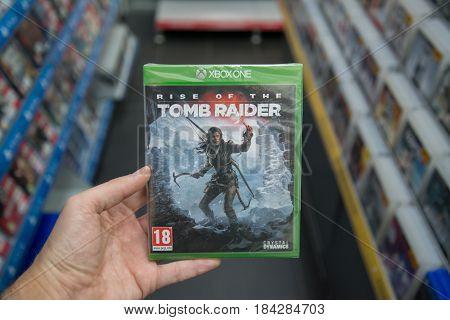 Bratislava, Slovakia, circa april 2017: Man holding Rise of the Tomb Raider videogame on Microsoft XBOX One console in store