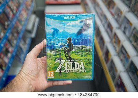 Bratislava, Slovakia, circa april 2017: Man holding The Legend of Zelda: Breath of the wild videogame on Nintendo WiiU console in store
