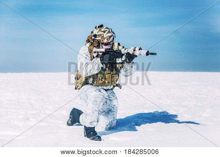 Army soldier with weapon in the Arctic. He wears chest rig, backpack, suffers from extreme cold, strong wind, but endures while mission continues, killing in snow desert. Shooting in kneeling position