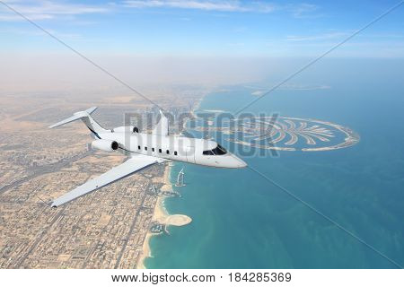 Business jet airplane flying over Dubai city and sea coastline.