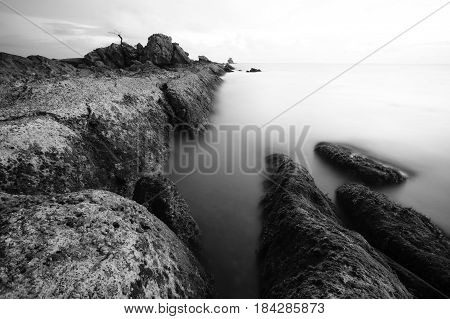 Beautiful Seascape,Ocean & Rocks at Sunset in black & white image.Known as Bonsai lonely tree Layang Layangan & lconic landmark in Labuan island,Malaysia.