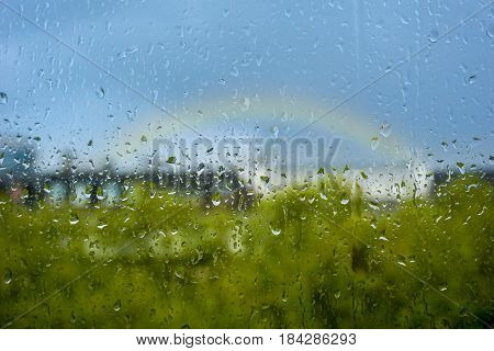 Close-up of Raindrops on a Window. Rain-drops on a Window in front of a Rainbow. Rainy Days. April Weather