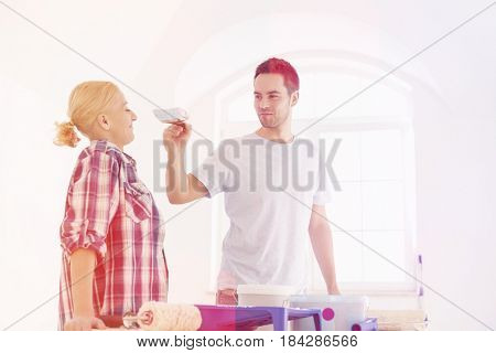 Playful man putting paint on woman's nose in new house