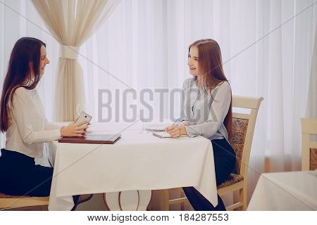two beautiful business girl sitting in the restaurant and at the table says