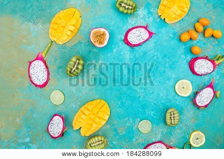Exotic fruits. Mango. Papaya. A pineapple. Kiwi. Pitahaya. Kumhvat. Copyspase. Fresh fruits. Exotic fruits on a the turquoise background. Blueberry. Strawberry. Physalis. Tamarind. Fruit slices. Lime. Lemon. Orange.