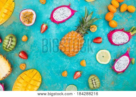 Exotic fruits. Mango. Papaya. A pineapple. Kiwi. Pitahaya. Kumhvat. Copyspase. Fresh fruits. Exotic fruits on a the turquoise background. Blueberry. Strawberry. Physalis. Tamarind. Fruit slices. Lime. Lemon. Orange.