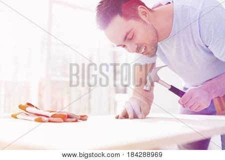 Mid-adult man nailing in table