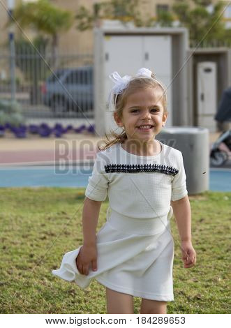 cute little girl smiling in a park blond in white dress