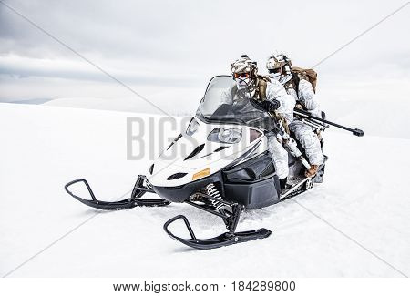 Army soldier in winter camo somewhere in the Arctic moving across the snow field riding tracked snowmobile