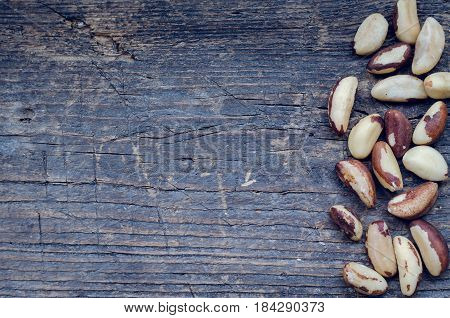 Tasty Brazil nuts from Bertholletia excelsa tree on the old wooden background with place for text. Healthy edible seeds food ingredient on the table. Top view. Copy space.