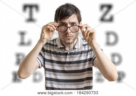 Man With Glasses Is Testing His Sight. Chart For Eye Sight Testi