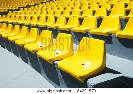 Yellow plastic chairs in a row. Abstract background