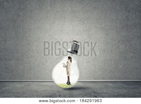 Businesswoman inside of light bulb in empty concrete room
