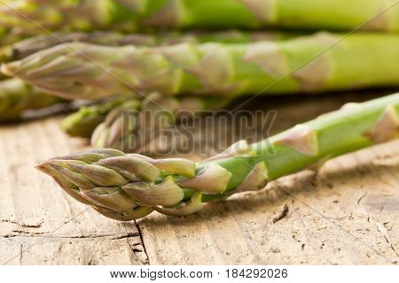 Bundle of fresh cut raw uncooked green asparagus vegetable on rustic wood table background - selective focus on tip of the bud