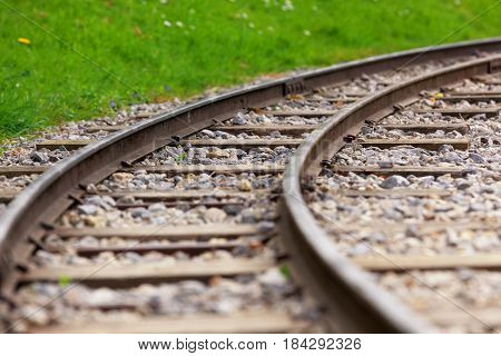 Railway line curving round into the distance with grass in the background and space for text. Shallow depth of field.