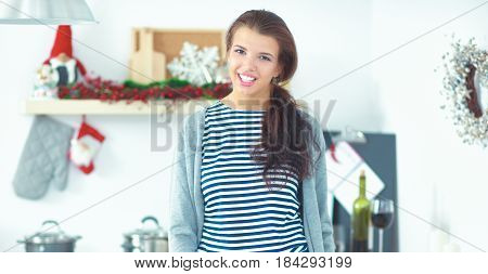 Portrait of young woman  against kitchen interior background.