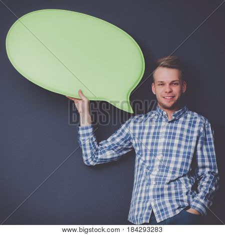 man holding white blank speech bubble with space for text