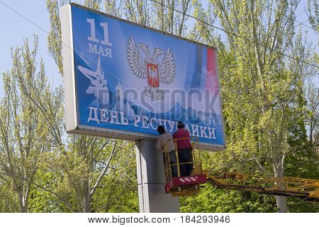 Donetsk Ukraine - April 29 2017: Workers glue Banner in the process of preparing for the celebration of the Day of Donetsk People's Republic which will be held on May 11