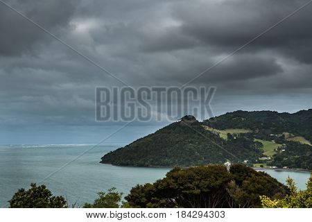 Auckland New Zealand - March 2 2017: Whatipu point at entrance from Tasman Sea into Huia Bay under heavy cloudscape. Green foliage green-gray waters.