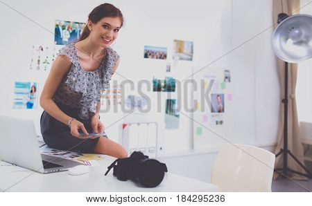 Young woman photographer processing pictures sitting on a desk.
