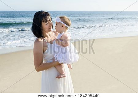 Mother is holding her baby girl on the sandy beach near ocean on a sunny day. Mother's day concept.