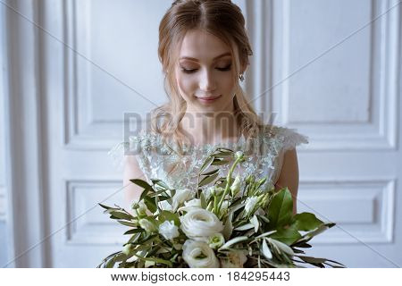 Beauty bride in bridal gown with bouquet indoors. Beautiful model girl in a white wedding dress. Female portrait of cute lady. Woman with hairstyle