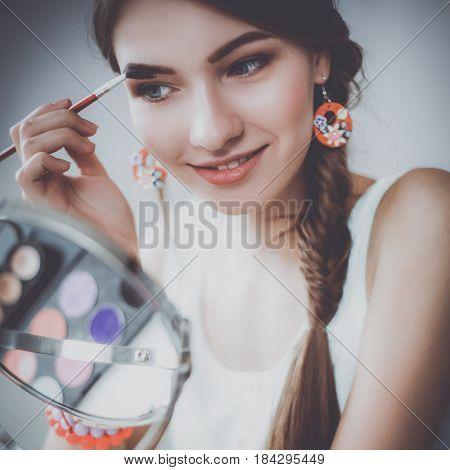 Young beautiful woman applying make up near mirror.