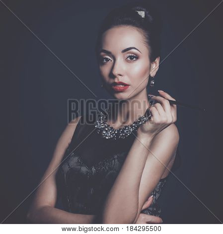 Retro woman portrait standing on the black background.
