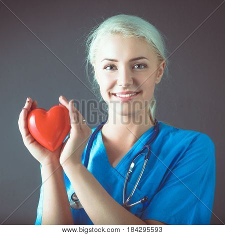 Young doctor woman with stethoscope holding a red heart.