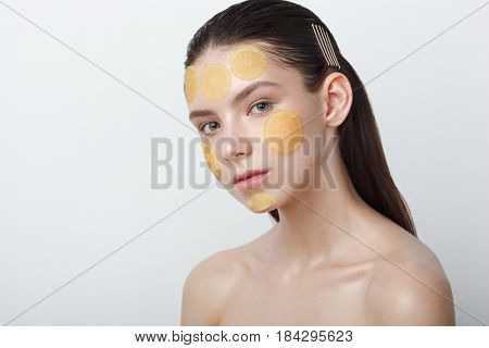 Beautiful young cheerful woman with refreshing mask on her face isolated on white background, copy space