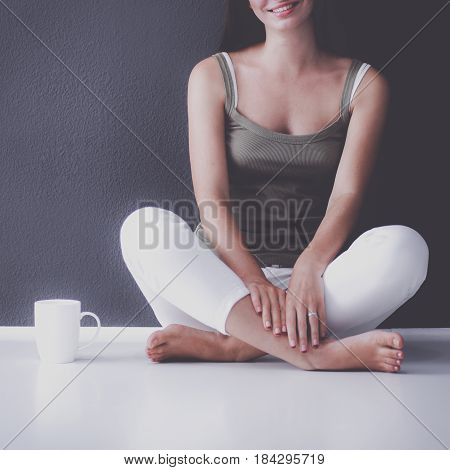 Attractive caucasian girl sitting on floor with cup near wall.