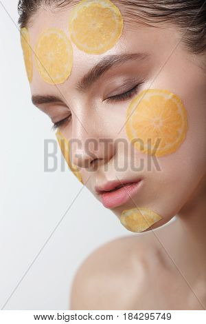 Beautiful young cheerful woman with refreshing mask on her face isolated on white background, she close her eyes
